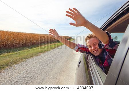 Boy putting his heads and hands out of the car window driving down a country road