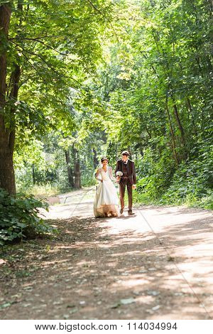 happy bride and groom walking in summer forest. Young wedding couple.