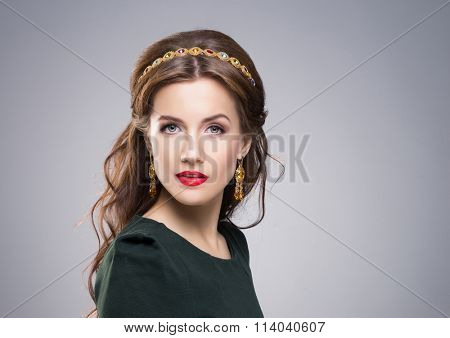 Portrait of gorgeous brunette wearing luxury golden coronet and earrings over isolated background.