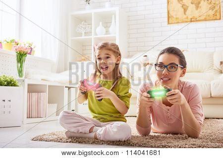 happy family together. mother and her child girl playing video games. family relax.