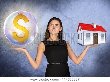 Woman holding dollar sign in bubble and house
