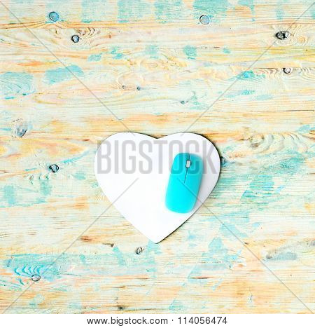 heart shaped pad with mouse on wooden background