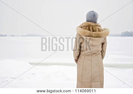 Woman Close To The Frozen River In Winter