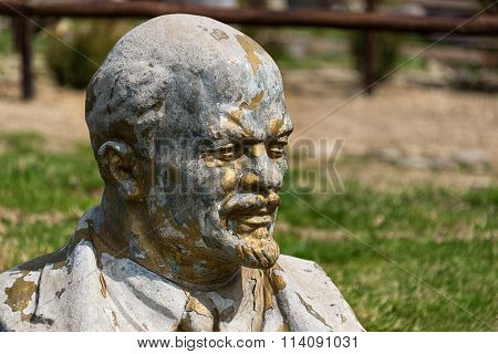 Abandoned and forgotten vandalized bust of Lenin standing on the grass near the tourist complex in the Carpathians Ukraine