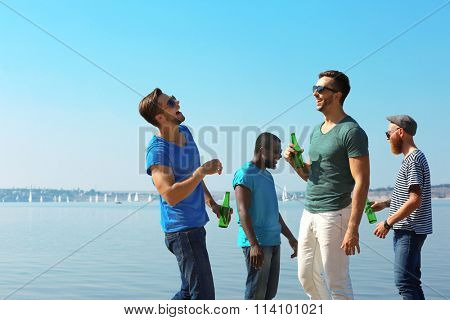 Young men drinking beer on the riverside