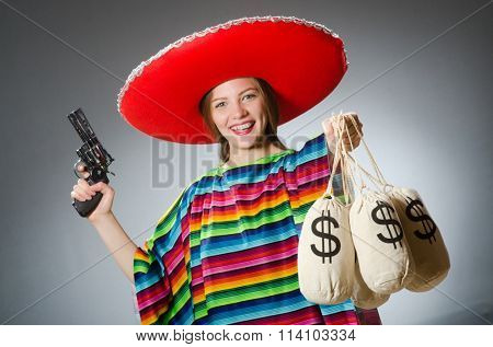 Girl in mexican poncho holding handgun and money sacks against g