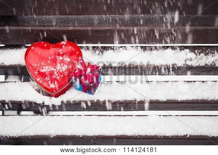 Red Heart Shaped Tin Box And A Gift Box On A Bench Covered With Snow
