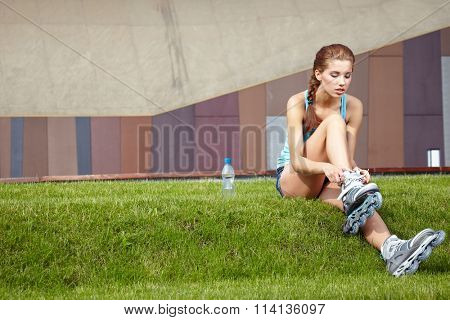 Woman skating in city. Girl going rollerblading sitting in grass putting on inline skates.