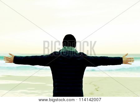 closeup of a young caucasian man seen from behind wearing scarf, a knit cap and a coat with his arms in the air in front of the ocean, feeling free