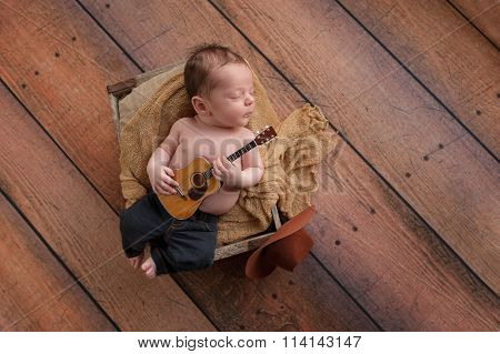 Newborn Baby Boy Playing A Tiny Guitar