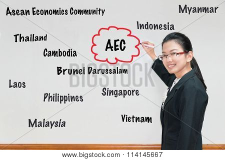 Asian Woman teacher writing AEC and member wording in whiteboard poster
