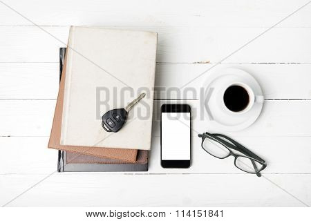 coffee cup with phone car key eyeglasses and stack of book on white wood table