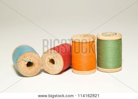 Several Spools Of Thread Of Different Colors On A White