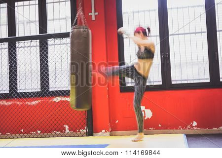 Beautiful Girl Boxing Against Punching Bag (intentionally Blurred)
