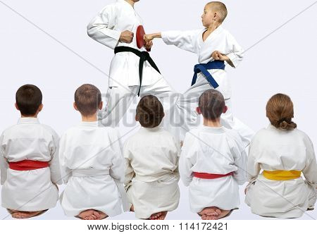 Children sit in a pose of looking on demonstration punch of karate