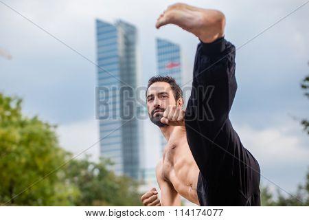 Sportsman doing karate kick in city downtown