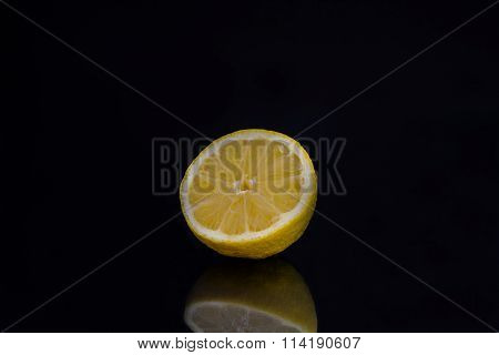Half a lemon in front of a black background