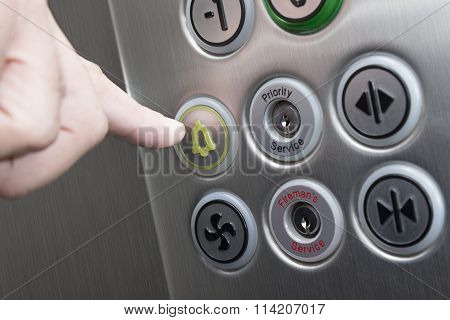 Forefinger pressing the alarm button in the elevator