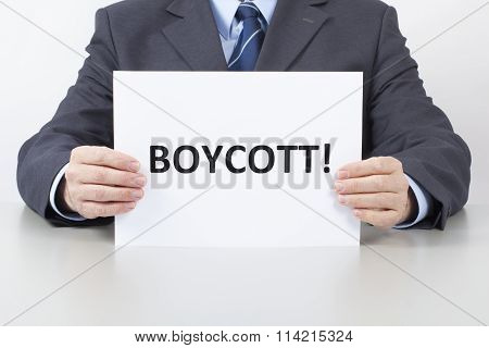Man Holds A Sheet With A Text Boycott
