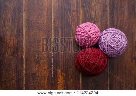 Three Skeins In Red And Pink Tones Over Wooden Background