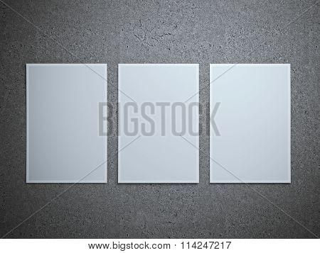 Three paper sheets on gray floor.
