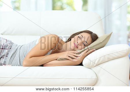 Beautiful girl sleeping or napping happy on a comfortable couch at home poster