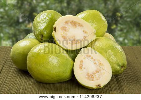 White Guava Cut In A Alf On A Plantation Background.