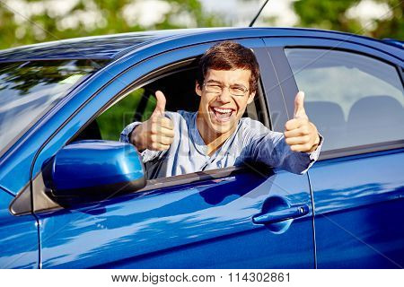 Close up of young happy hispanic man wearing glasses showing thumb up hand gesture with both hands and laughing through car window - new drivers concept