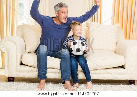 Father and son exulting on the sofa while holding football ball