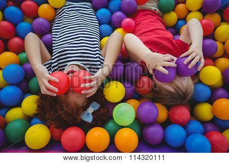 Cute smiling girls in sponge ball pool covering eyes with balls