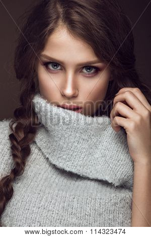 Beautiful young girl with gentle make-up in warm sweater and long straight hair. Beauty face.