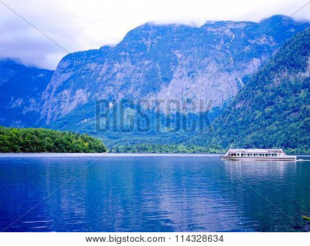 Hallstatt Tourist Boat Cruising In The Lake With Foggy View Of Alphine