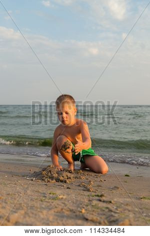 Boy 5 years playing in the sand, sea vacation.