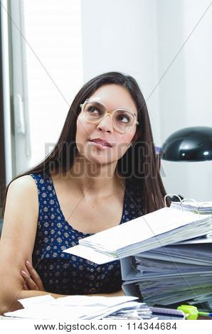 Hispanic brunette wearing glasses sitting by office desk with papers around