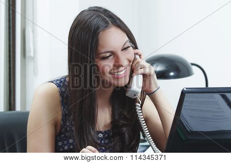 Hispanic brunette sitting by office desk talking on telephone smiling with positive attitude