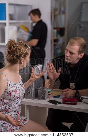 Police Officer Interrogating Young Woman