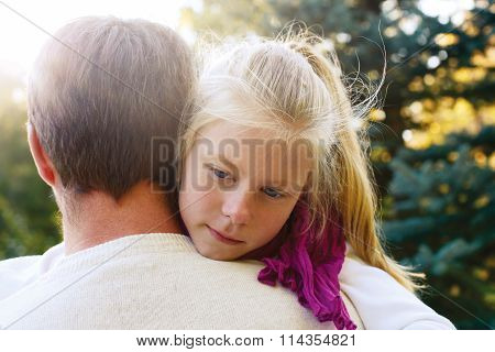 Daddy Reassured His Daughter. Little Girl Resting On Her Father's Shoulder