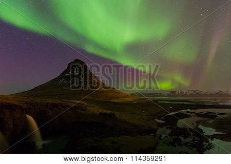 Beautiful northen lights over Kirkjufell mountain and waterfalls