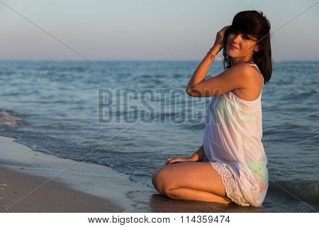 Beautiful young brunette in a white tunic on the beach.
