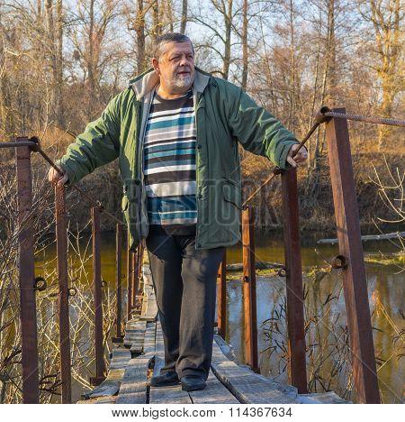 Senior man standing on a suspension bridge