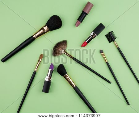 Different cosmetics on green texture a background