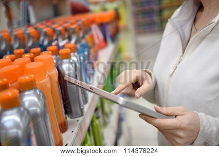 Woman merchandiser checking products available with digital tablet poster