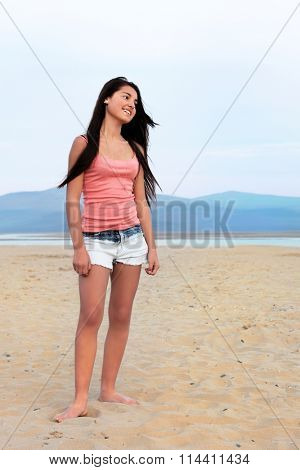 Young european teenage girl with long dark hair smiling and standing on a sandy beach.