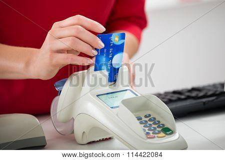 Saleswoman Swiping Credit Card On Reader