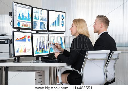 Financial Analysts Using Computers In Office