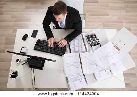 Businessman Analyzing Documents At Computer Desk