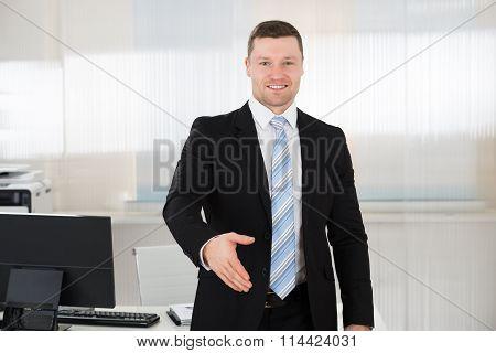 Happy Businessman Offering Handshake In Office