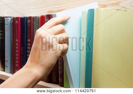 Women Hand selecting book from a bookshelf in library. Back to school.