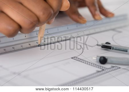 Person's Hand Drawing Blue Print