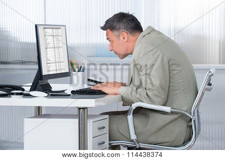 Concentrated Businessman Using Computer At Desk
